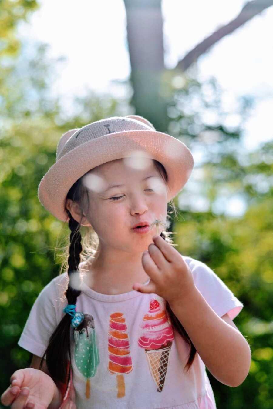 唐氏综合症的小女孩在吹在一件桃红色衬衣的蒲公英吹在有匹配的桃红色帽子的一件蒲公英
