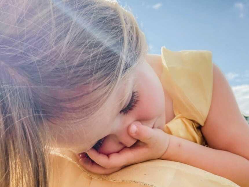 一个穿着黄色连衣裙的小女孩在散步时感到焦虑,蜷缩在地上