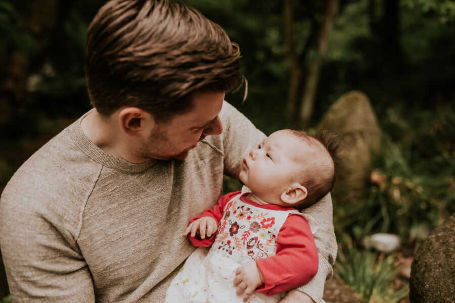 Dad smiles down at his medically complex daughter during a newborn photoshoot outside