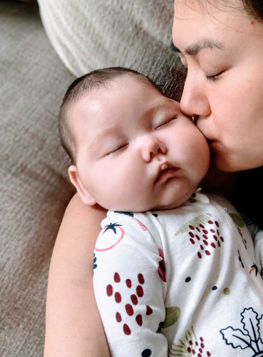 First time mom kisses her newborn daughters cheek while she sleeps