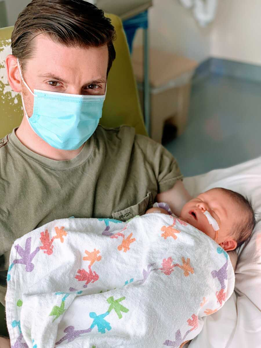 First time dad holds his newborn daughter while wearing a blue face mask