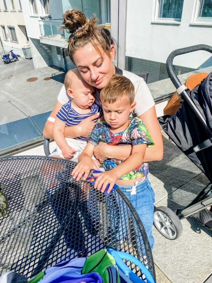 在瑞士度假的时候,妈妈抱着她的两个儿子坐在餐厅外面