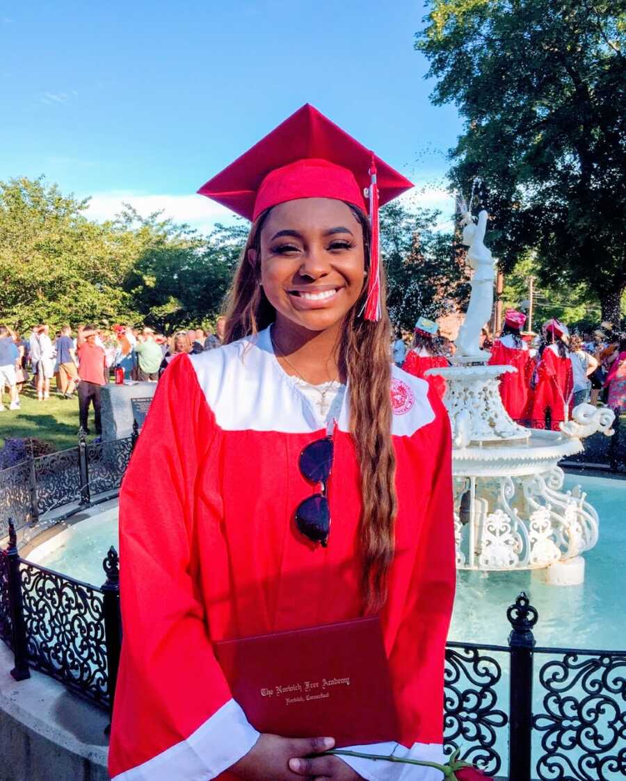 Young girl takes a photo at her high school graduation in a red cap and gown while holding her diploma