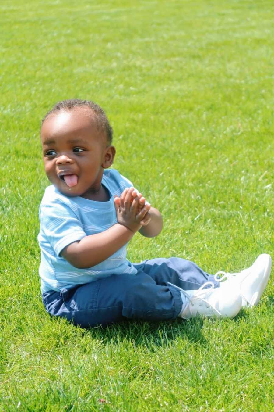 Young single mom takes a photo of her son clapping while enjoying the sunshine