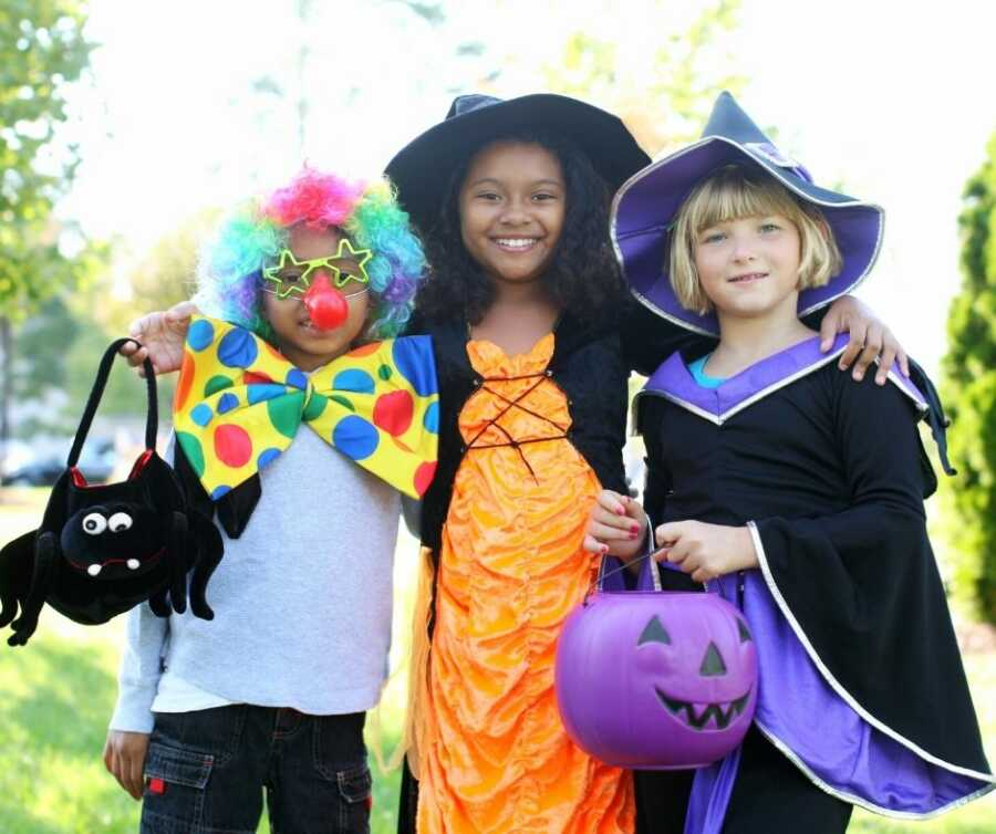 Three kids dressed in Halloween costumes get ready to trick-or-treat.