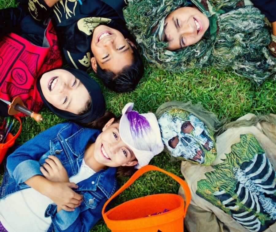 Children in Halloween costumes lay in a circle and smile up at the camera.