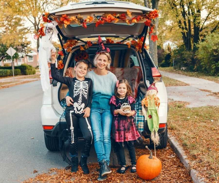 Mom and kids sit in the trunk of their car, all decorated for Halloween.