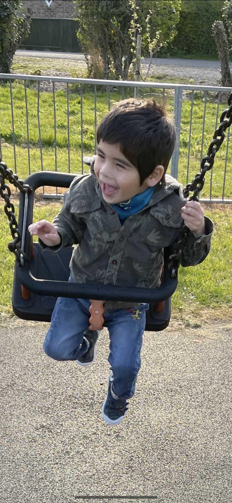 son having fun outside on the swing