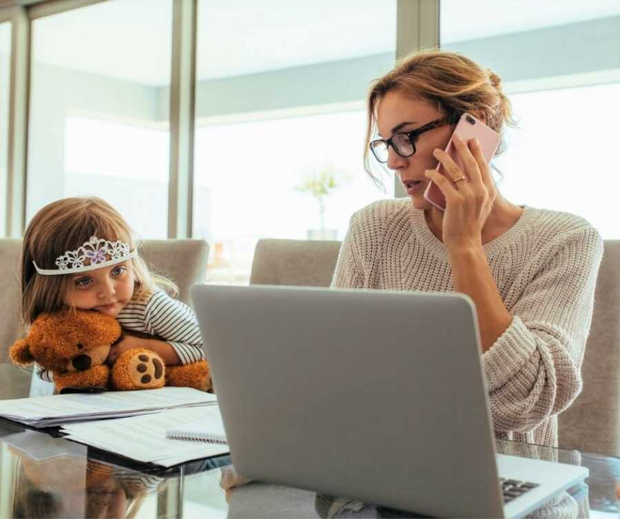 Little girl with tiara and teddy bear watches busy working mom.