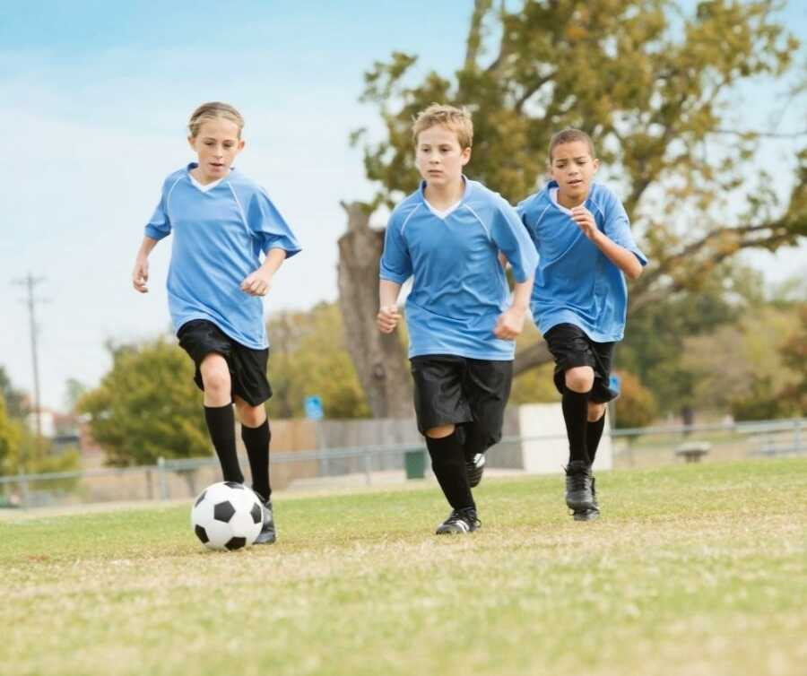 Three kids in blue jerseys chase after soccer ball.