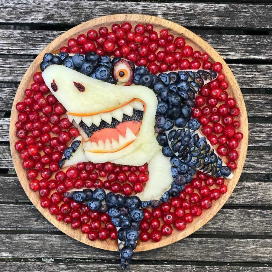 Edible food art fruit platter scene of a cartoon shark.