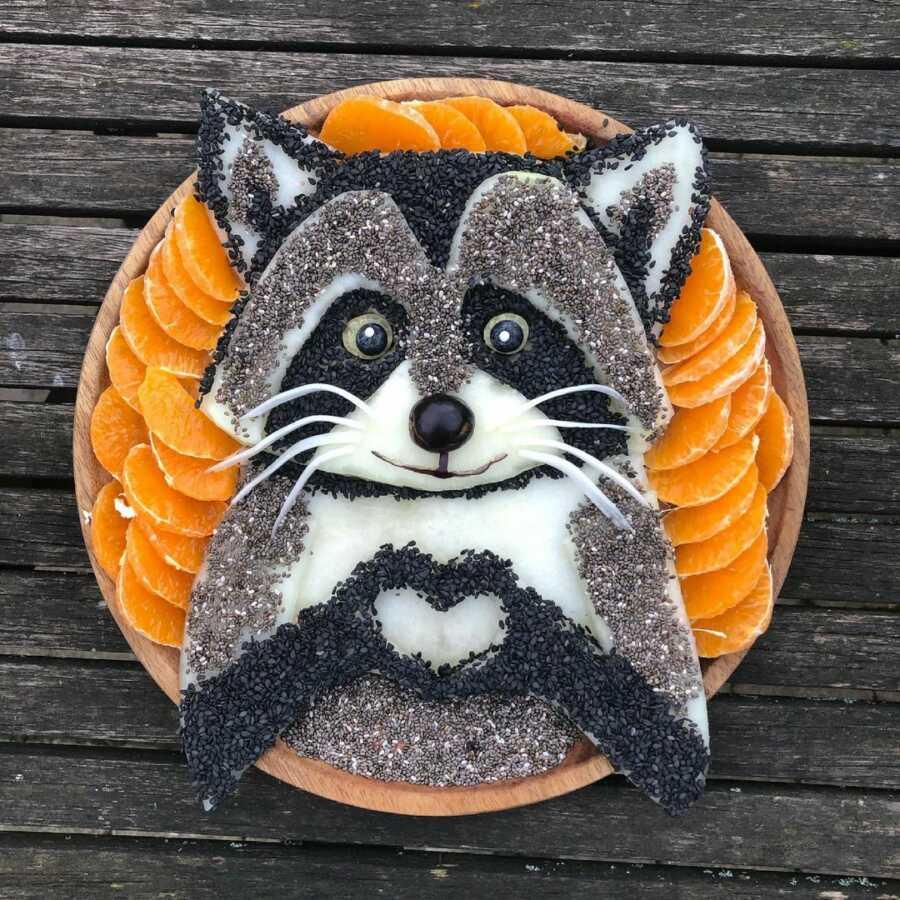Edible food art fruit platter scene of a racoon.