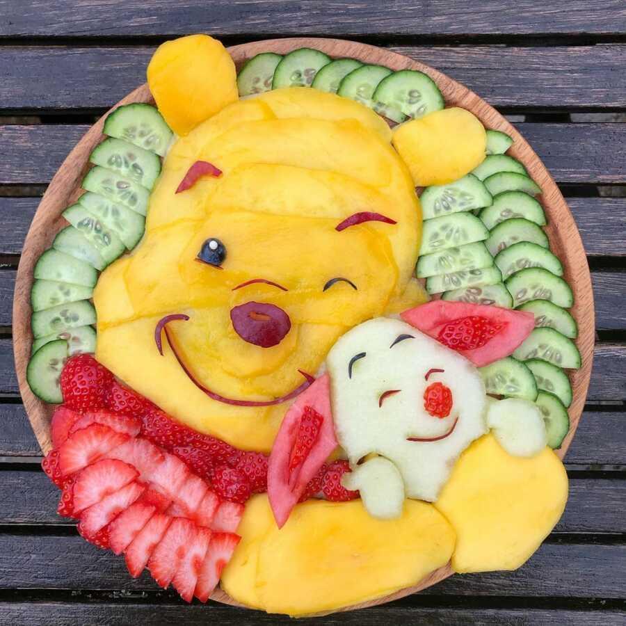 Edible food art fruit platter scene of Winnie the Pooh and Piglet.