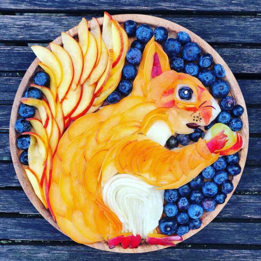 Edible food art fruit platter scene of a squirrel.
