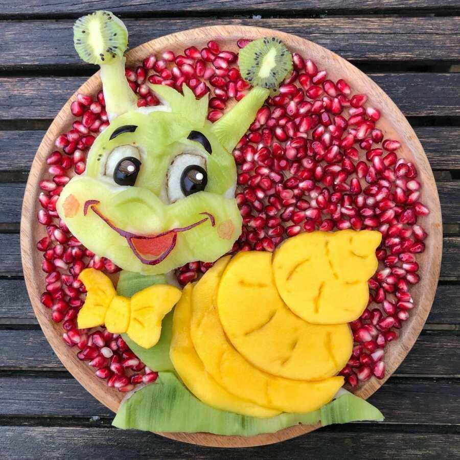 Edible food art fruit platter scene of a cute cartoon snail.