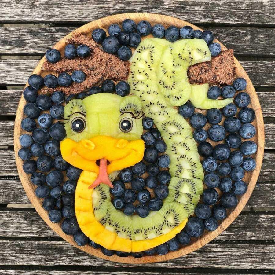 Edible food art fruit platter scene of a cartoon snake.