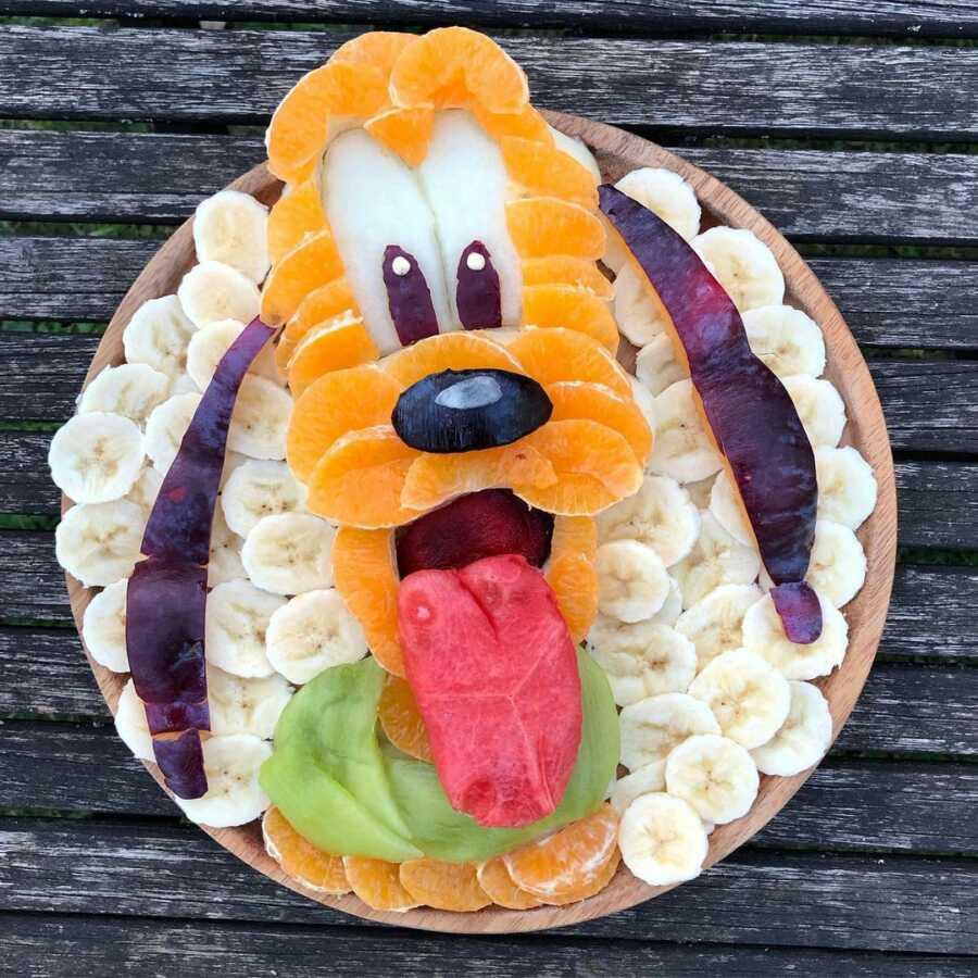 Edible food art fruit platter scene of Disney's Pluto.