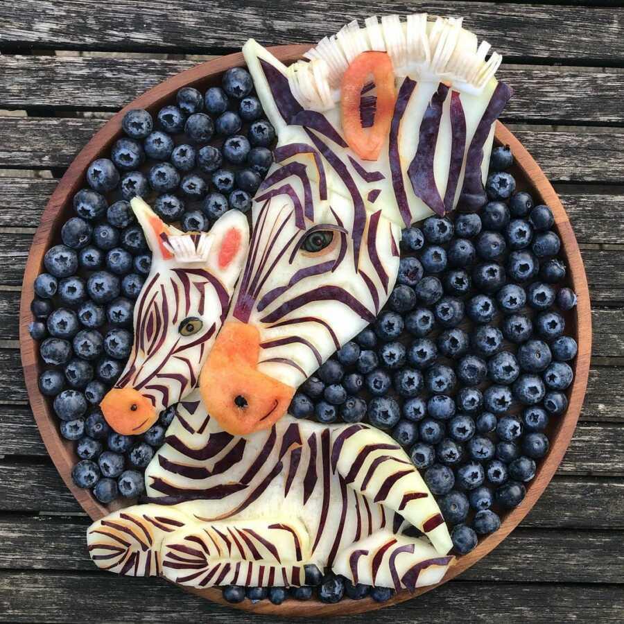 Edible food art fruit platter scene of a zebra with her baby.