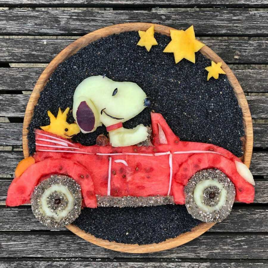 Edible food art fruit platter scene of Snoopy and Woodstock in a red car.
