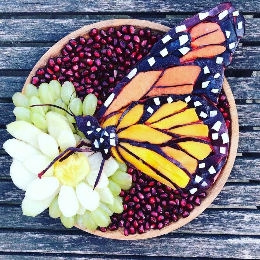 Edible food art fruit platter scene of a monarch butterfly.