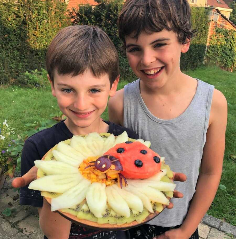 Sarah's boys hold up one of her fruit platter creations.