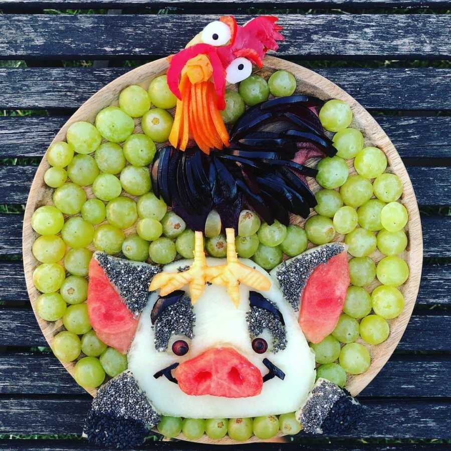 Edible food art fruit platter scene of Hei-Hei and Pua from Disney's Moana.
