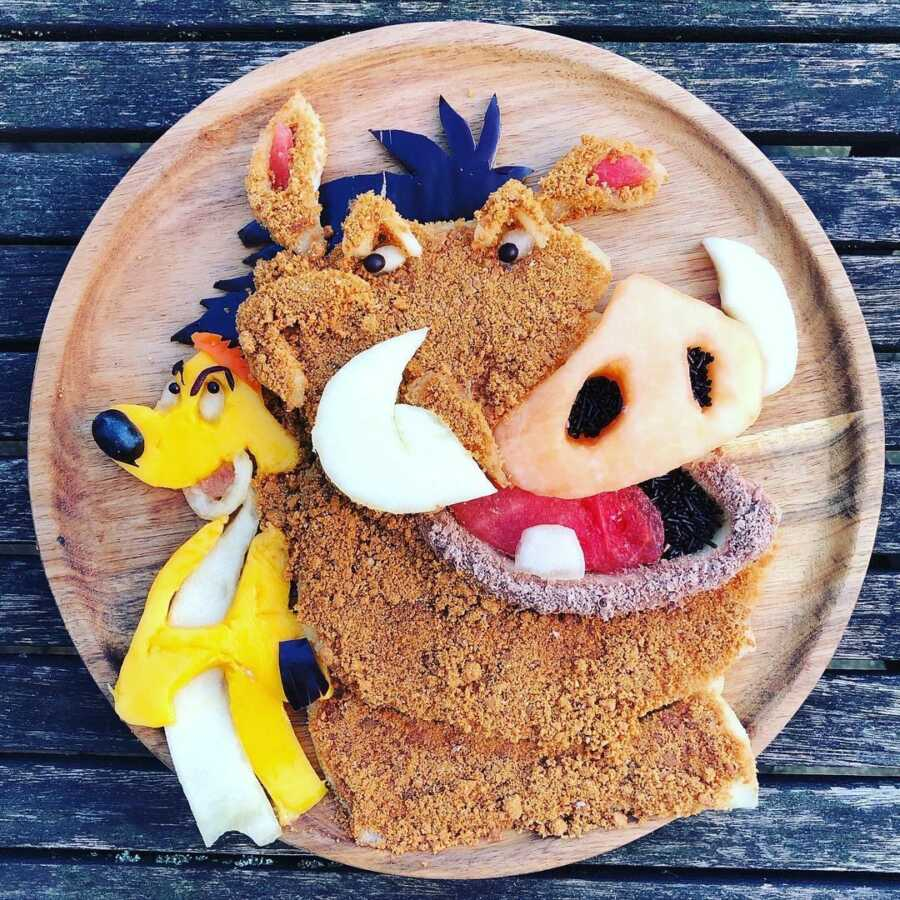 Edible food art fruit platter scene of Pumba and Timon from Disney's The Lion King.