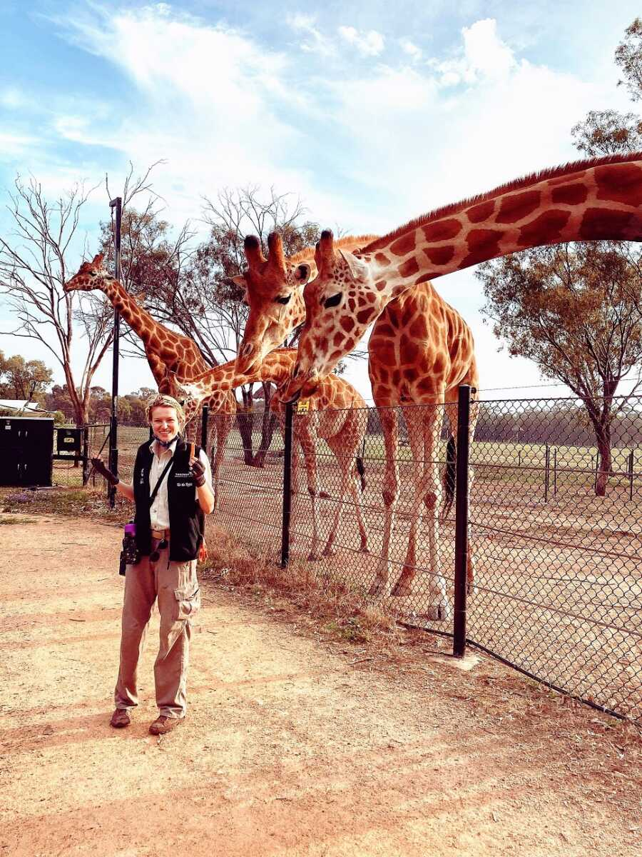 Woman working as a tour guide with giraffes