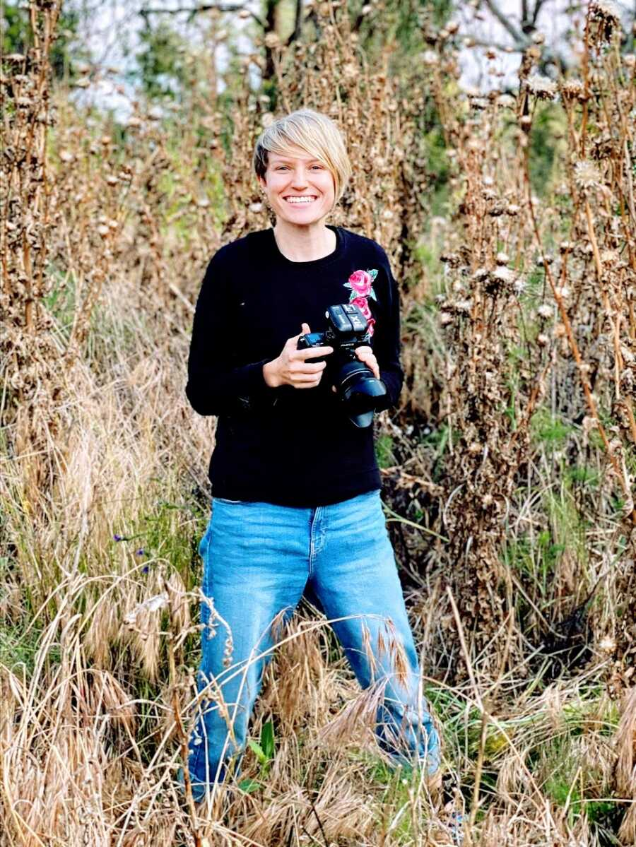 Woman holds camera out in field