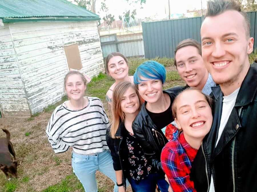Woman with blue hair stands with friends