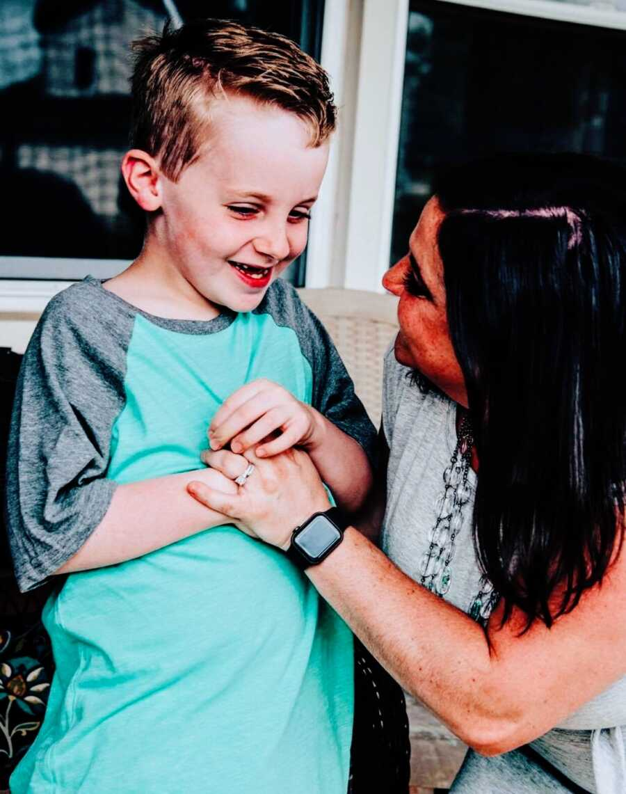 Mom puts hand on smiling son's chest