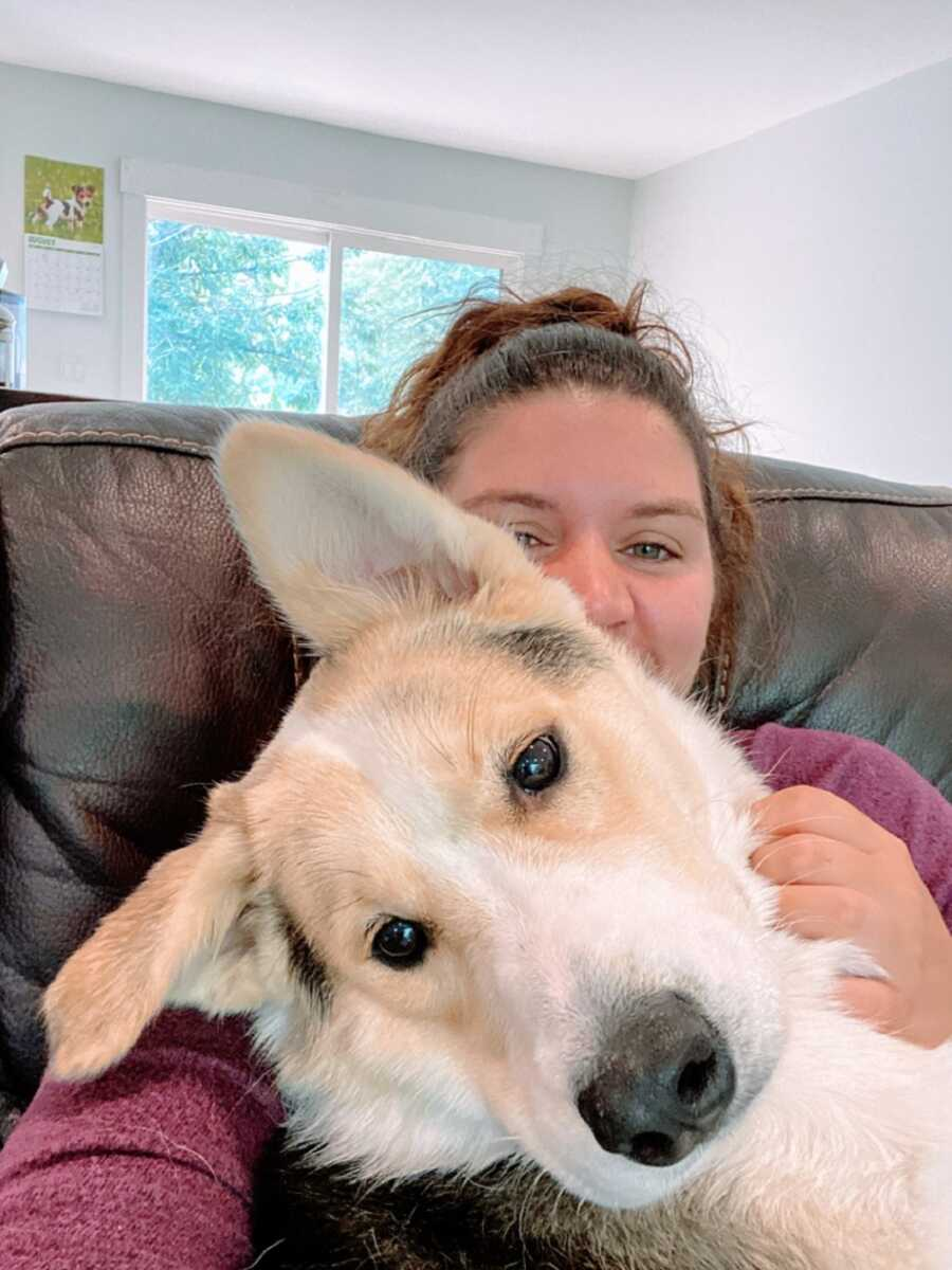 Woman sits on couch with big dog's head on lap