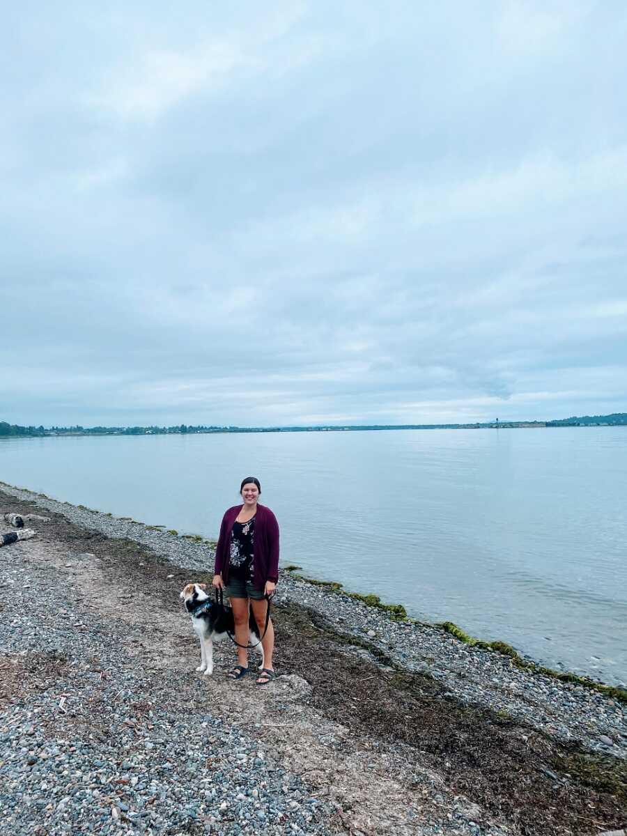 女人和狗站在海滩上
