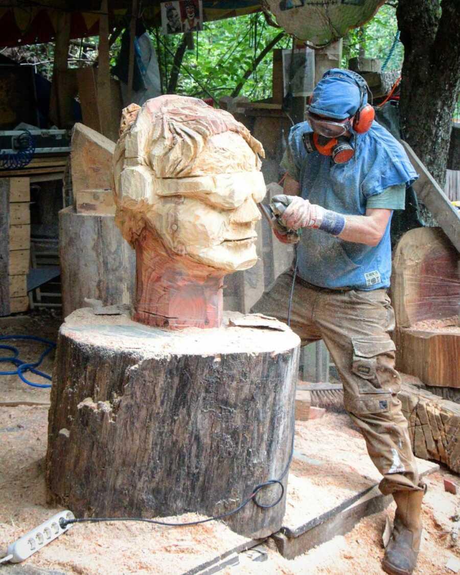 Artistic director, Pit Ruge, carves a giant wood sculpture for the pumpkin exhibition frames.