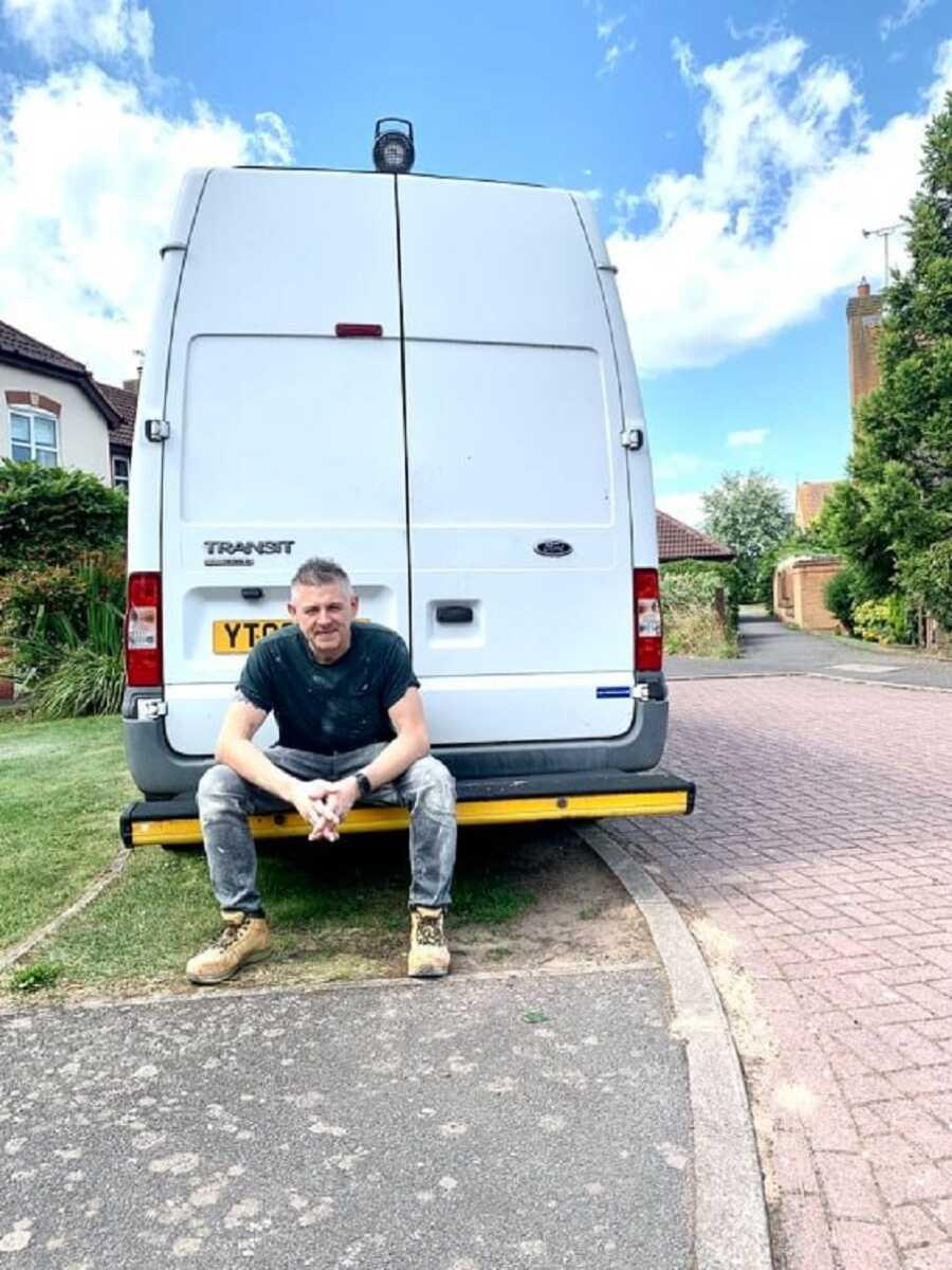 Plumber sits on the bumper of his work van, posing for the camera.