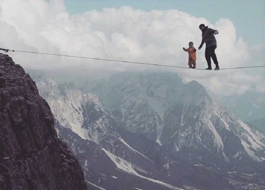 Dad and baby walk tight rope over mountain plunge.