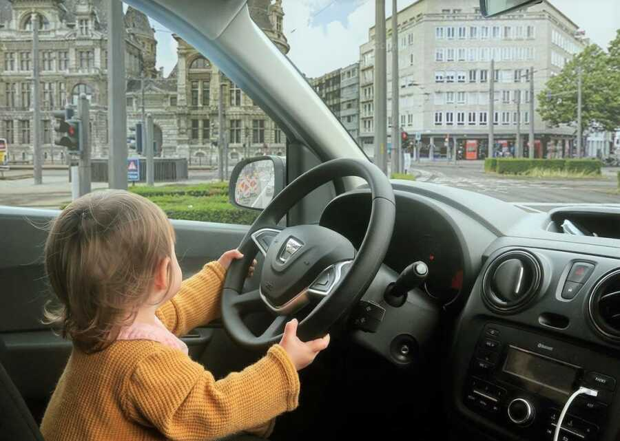 Toddler appears to be driving the car through city streets.