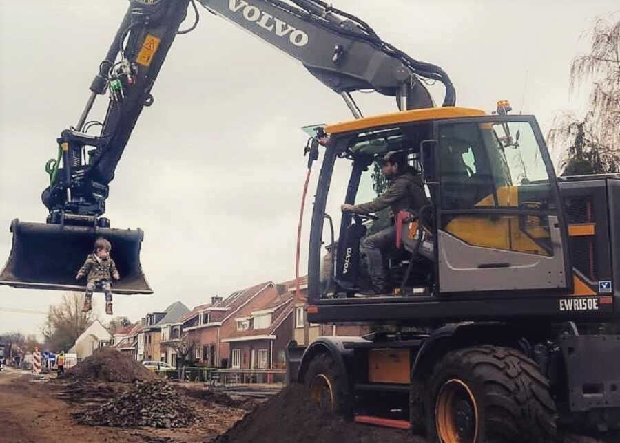 Dad creates picture scooping toddler up with construction excavator.