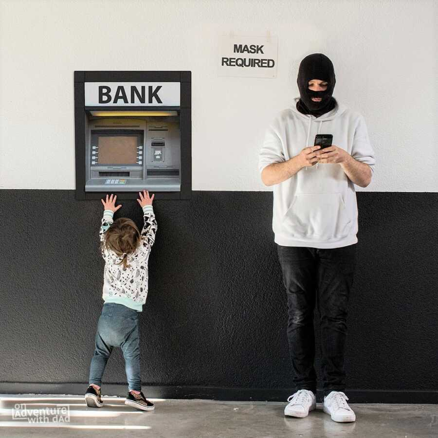Dad wears black ski mask while toddler reaches for the bank's ATM.