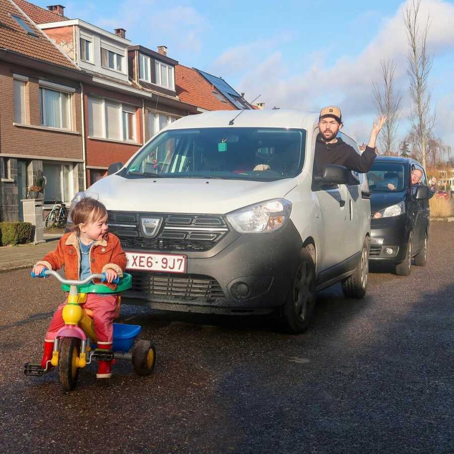 Cars line up in traffic jam behind a toddler on a plastic tricycle.