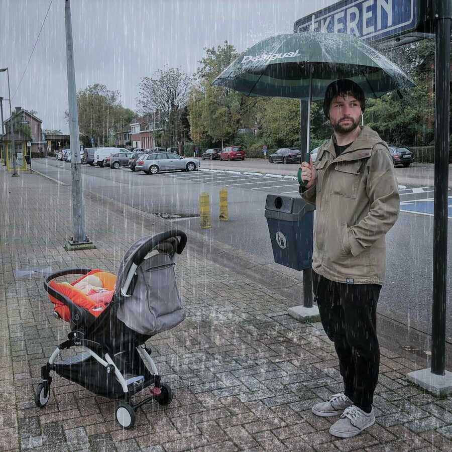 Dad takes picture in the rain, appearing to have remembered his own umbrella but not one for the baby.
