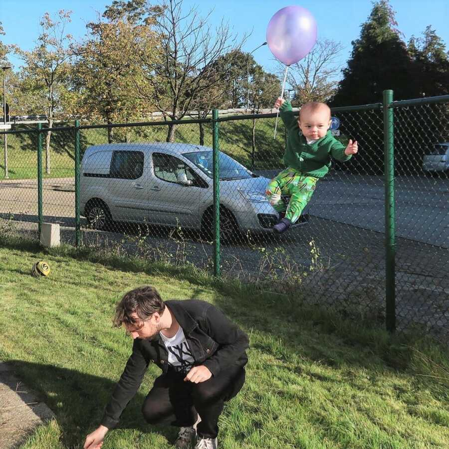Baby floats away with balloon while dad is distracted picking something up off the ground.