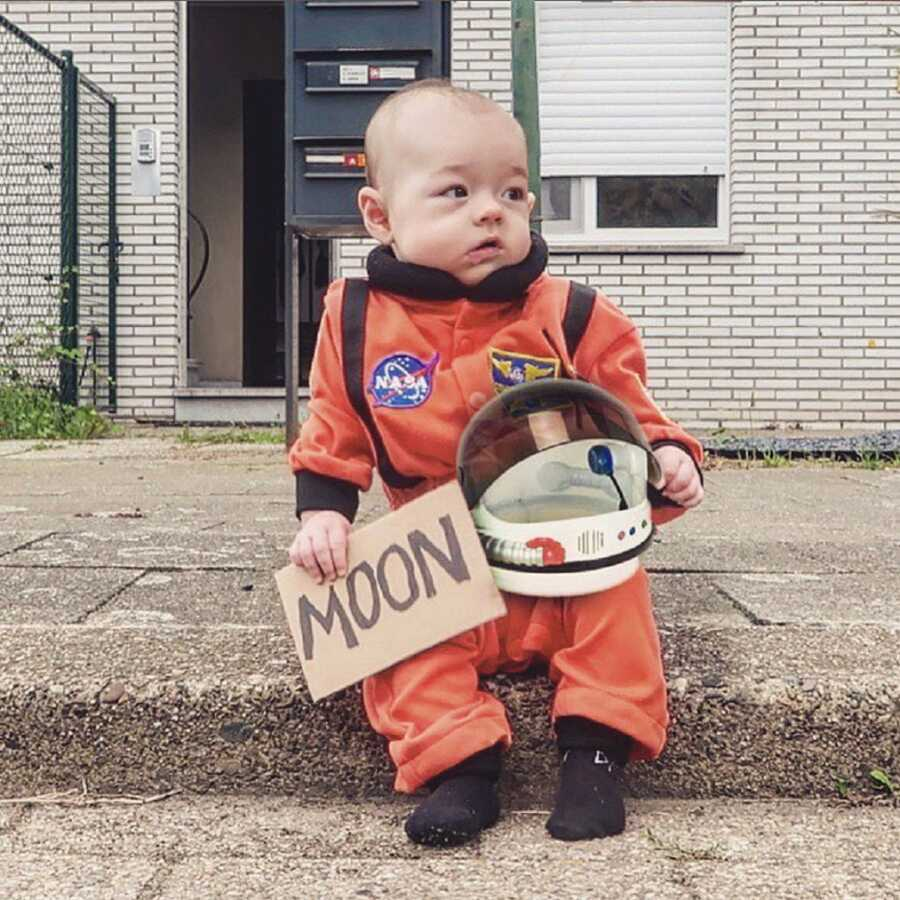 Small baby sits on the sidewalk curb in a space suit, trying to hitch hike to the moon.