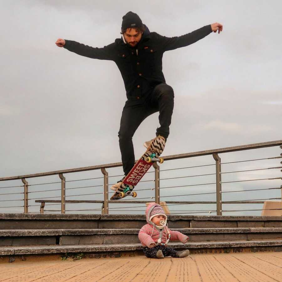 Dad creates picture performing skate board trick jumping over baby.