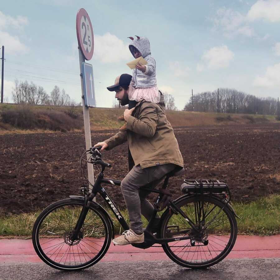 Dad rides bicycle with toddler balanced on his shoulders.