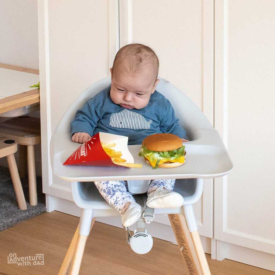 Dad jokingly feeds infant baby hamburger and fries.