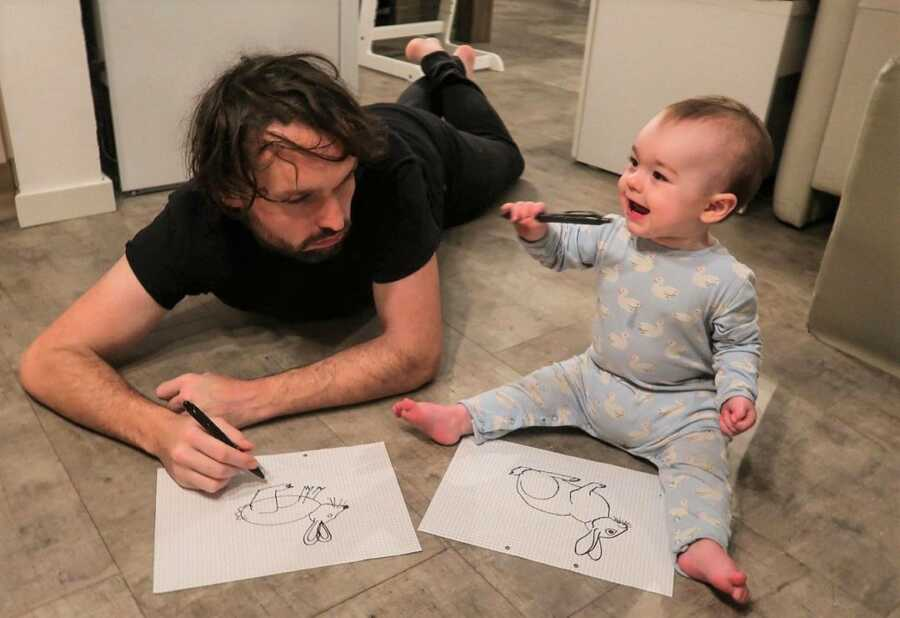 Dad looks at baby's drawing of a rabbit, which is much better than his.