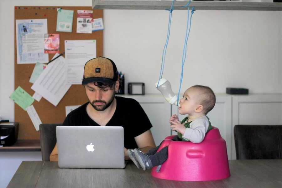 Dad suspends baby's bottle so they can feed themselves while he works.