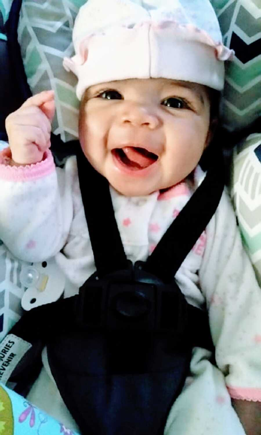Little girl makes silly face in carseat
