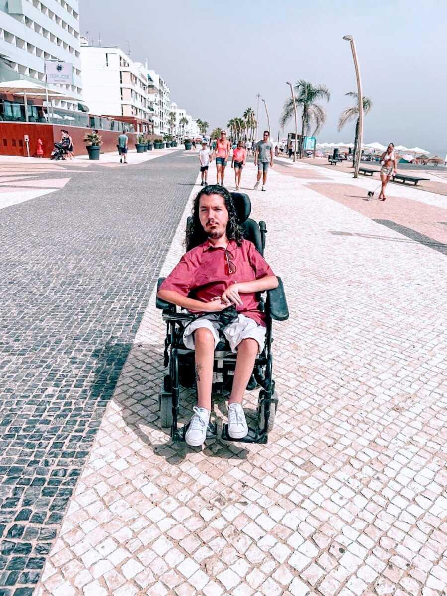 Man in wheelchar outside near a beach